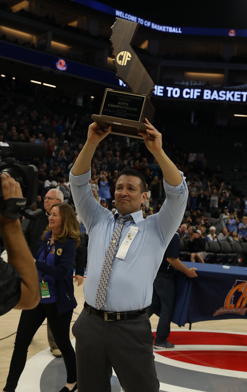 . Pleasant Valley High coach Tim Keating proudly holds the trophy in the air, March 24, 2018, in Sacramento, California. (Carin Dorghalli -- Enterprise-Record)