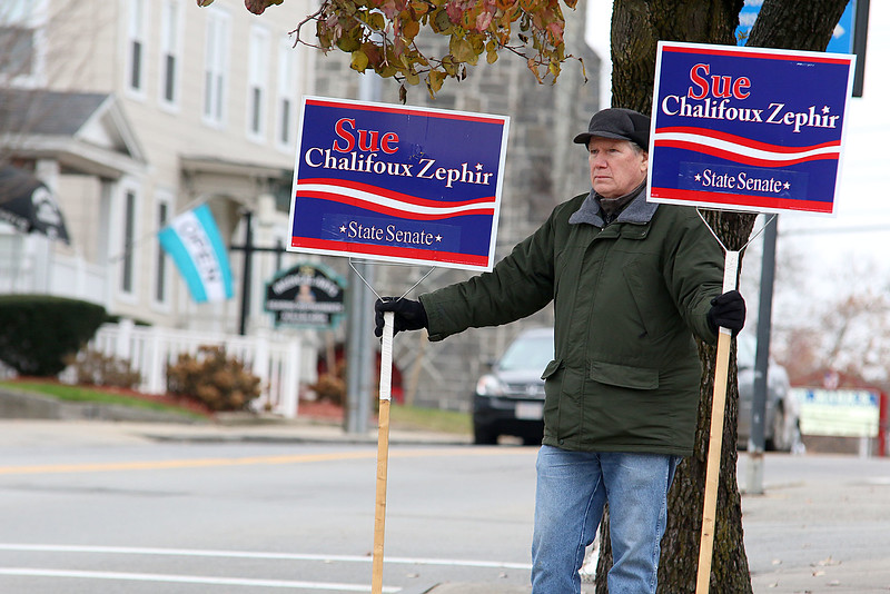 Don Ciprotti hold some signs for Sue Chaligoux Zaphir at the polls at Leominster City Hall on Tuesday December 5, 2017 during the Worcester Middlesex District State Senate race. SENTINEL & ENTERPRISE/JOHN LOVE