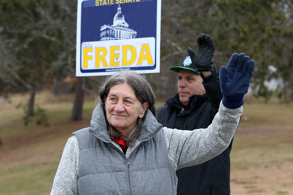 . Candidate Claire Freda waves to voters the polls at Memorial Middle School in Fitchburg on Tuesday December 5, 2017 during the Worcester Middlesex District State Senate race as she hangs out with supporter John DeCicco. SENTINEL & ENTERPRISE/JOHN LOVE