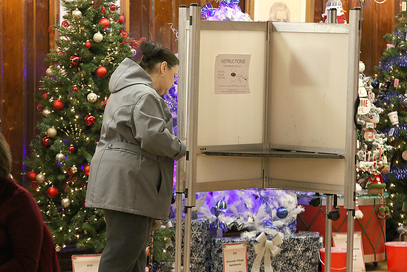 John R. Tata Auditorium was decked out with festive Christmas trees at Leominster City Hall on Tuesday December 5, 2017 during the Worcester Middlesex District State Senate race as voter Jeanne Colton filled out her ballot. SENTINEL & ENTERPRISE/JOHN LOVE
