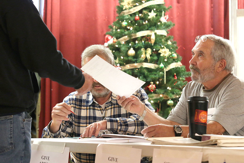 . Election Worker Frank Giangrando hands a ballot to a voter  at the polls in Leominster City Hall on Tuesday December 5, 2017 for the Worcester Middlesex District State Senate race. SENTINEL & ENTERPRISE/JOHN LOVE