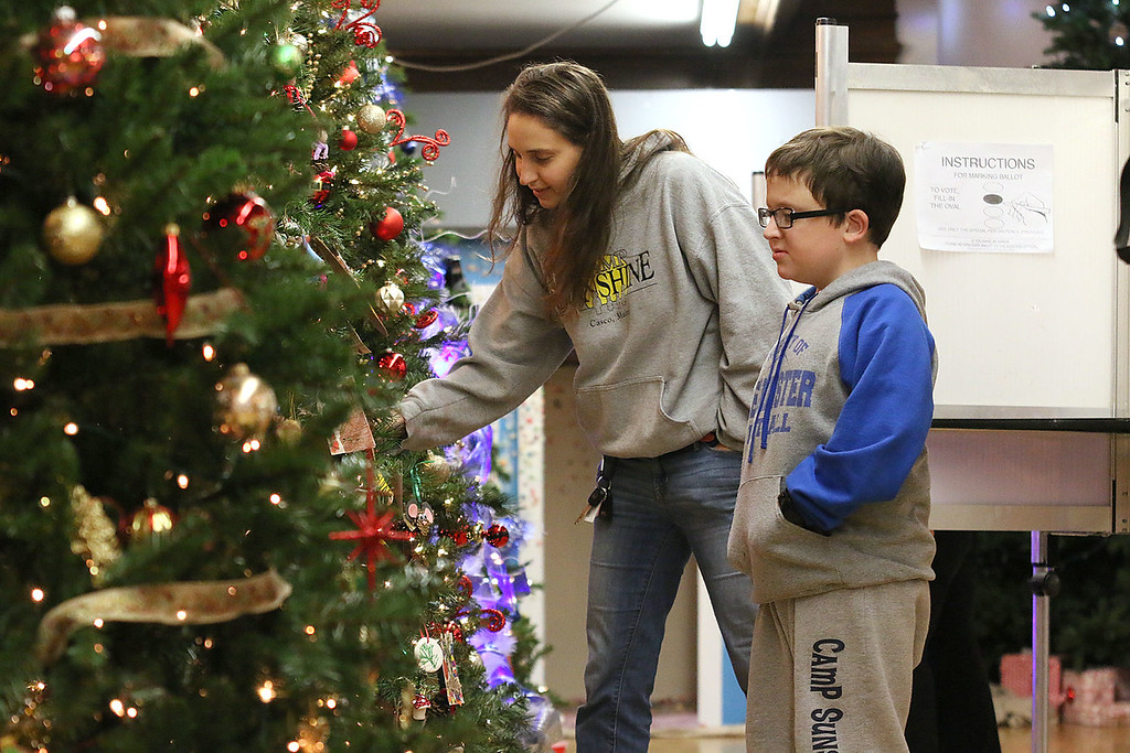 . Tommy Joffrion, 11, and his mom Maria Joffrion browse the Christmas trees in the John R. Tata Auditorium at Leominster City Hall on Tuesday December 5, 2017 just after she voted in the Worcester Middlesex District State Senate race. SENTINEL & ENTERPRISE/JOHN LOVE