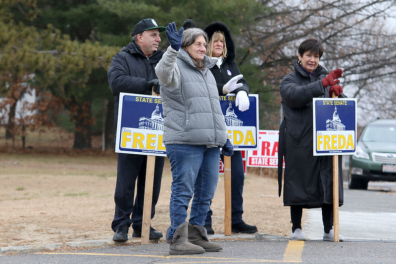 Candidate Claire Freda waves to voters the polls at Memorial Middle School in Fitchburg on Tuesday December 5, 2017 during the Worcester Middlesex District State Senate race as she hangs out with supporters John DeCicco, Kim Mazzarella and Peg Padovano. SENTINEL & ENTERPRISE/JOHN LOVE