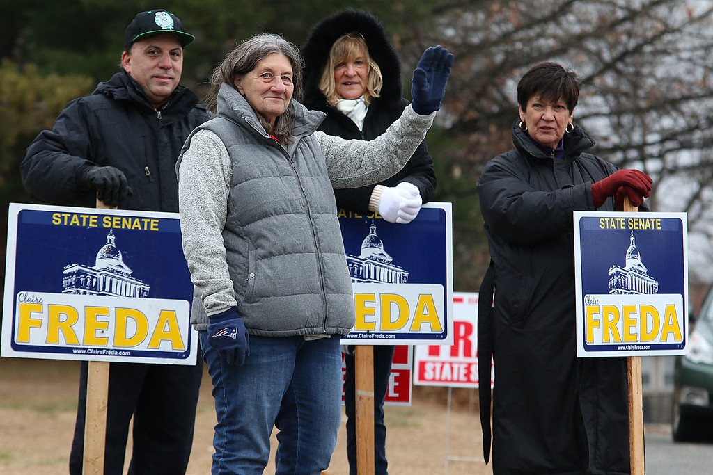 . Candidate Claire Freda waves to voters the polls at Memorial Middle School in Fitchburg on Tuesday December 5, 2017 during the Worcester Middlesex District State Senate race as she hangs out with supporters John DeCicco, Kim Mazzarella and Peg Padovano. SENTINEL & ENTERPRISE/JOHN LOVE