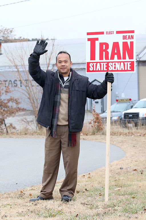 . Candidate Dean Tran waves to voters out in front of the polls at the St. Bernard\'s Activity Center in Fitchburg on Tuesday December 5, 2017 during the Worcester Middlesex District State Senate race. SENTINEL & ENTERPRISE/JOHN LOVE