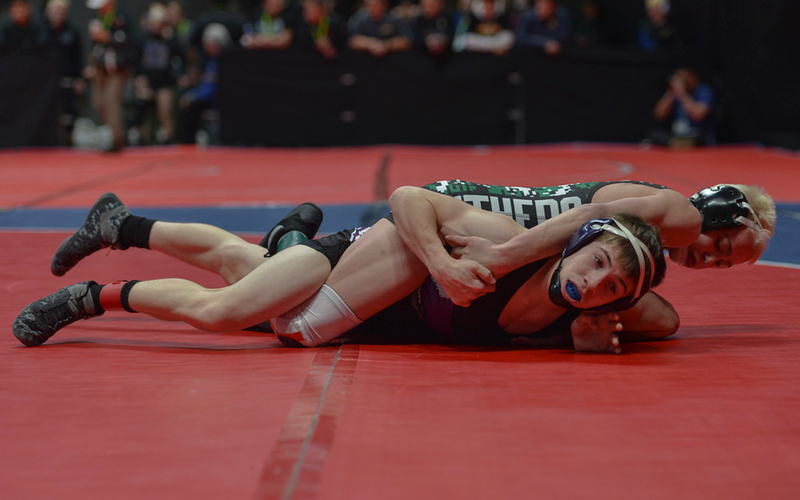 Kitchen struggles to break free from Brady Hankin's tight grasp during his second-round match at the 2019 CHSAA 3A State Wrestling Championships at the Pepsi Center.