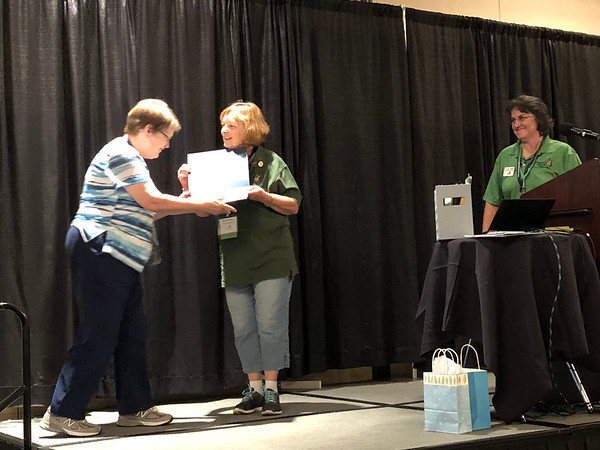 Rosemarie Nielsen receives photo contest award.