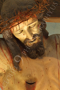 SpMis 00251 A vertical tight crop of the crown of thorns and a spear wound in an artistic representation of a crucified Jesus Christ above the altar at Mission San Louis Rey, by Peter J Mancus