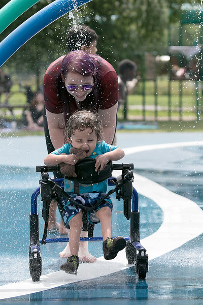 The Parkhill Park water spray park in Fitchburg was full of kids trying to stay cool on Wednesday. Katie Mays helps her son Richie, 3, both of Fitchburg stay cool during their visit to the park. Richie is in a walker because he has Osteogenesis Imperfecta or brittle bone disease. SENTINEL & ENTERPRISE/JOHN LOVE