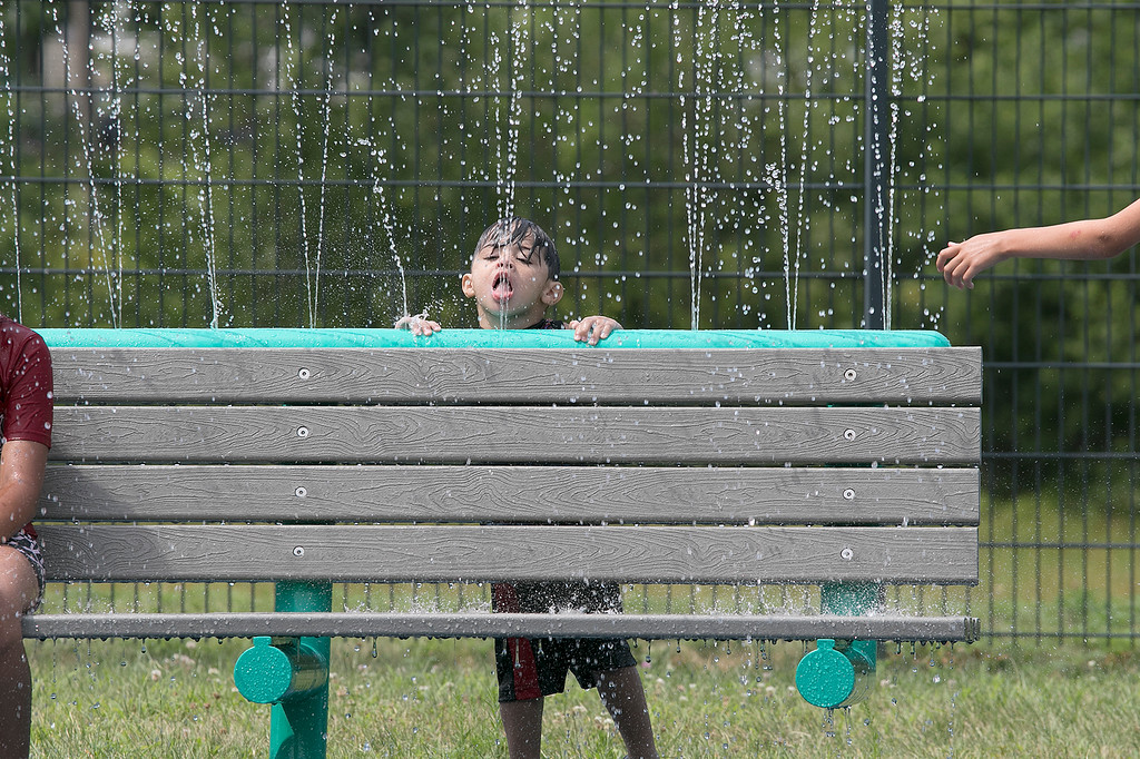 . The Parkhill Park water spray park in Fitchburg was full of kids trying to stay cool on Wednesday. Taylor Gendron, 2, of Fitchburg sticks his tongue out to catch some water spraying from a bench at the park. SENTINEL & ENTERPRISE/JOHN LOVE