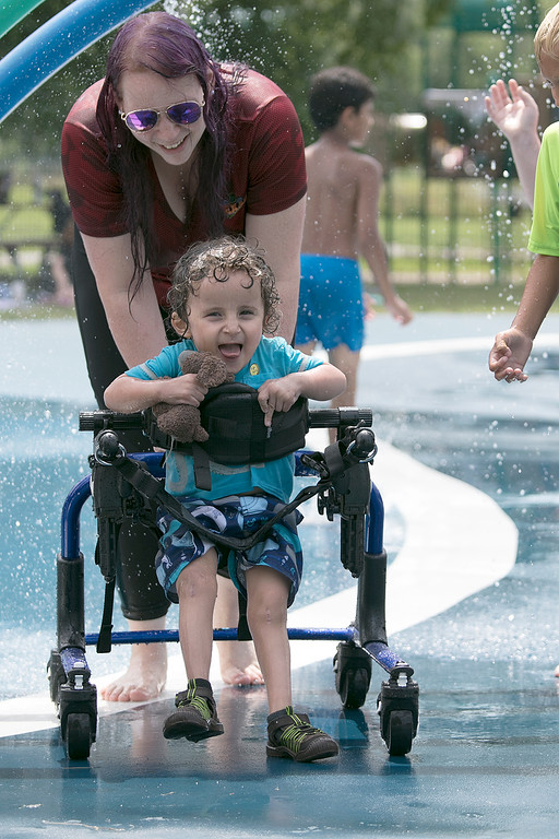 . The Parkhill Park water spray park in Fitchburg was full of kids trying to stay cool on Wednesday. Katie Mays helps her son Richie, 3, both of Fitchburg stay cool during their visit to the park. Richie is in a walker because he has Osteogenesis Imperfecta or brittle bone disease. SENTINEL & ENTERPRISE/JOHN LOVE