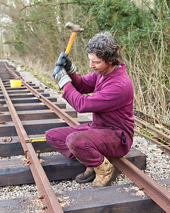 Hammering the pins in - two in the outside and one on the inside of the rail