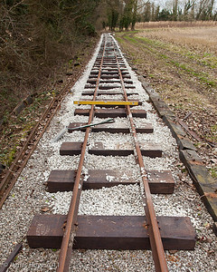 As the track is ballasted, a check on the level is kept and adjusted if necessary by jacking the track and tamping more ballast under the offending sleepers