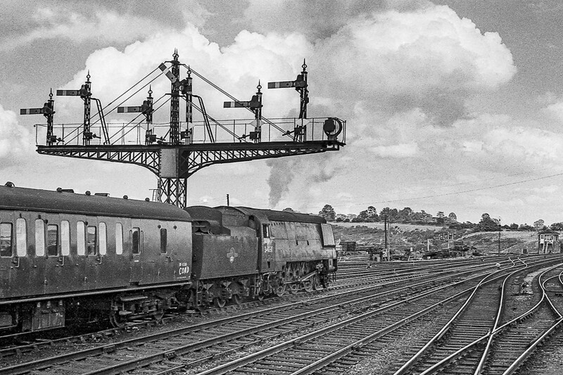 28th Aug 1964:  34030 'Watersmeet' is getting underway from Yeovil Junction with a rake of condemned coaching stock.  Nothing very special but the gantry and the sky make it something special.  IMHO.