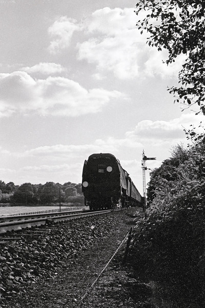 Au 1964: An unrebuilt West Country class 4-6-2 passes the Distant on the climb to Battledown flyover