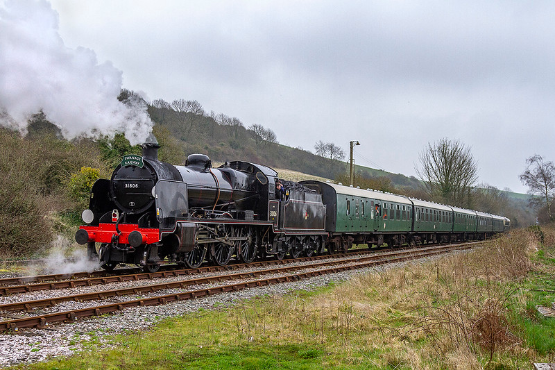 13th Apr 2018:   Leaving Maiden Newton on the rear of 5Z43 is Class U 2-6-0 31806 that is undertaking a test run on the main line between it's base Swanage and Yeovil Junction.  Hopefully it passes the test and we see it out on the main line soon.