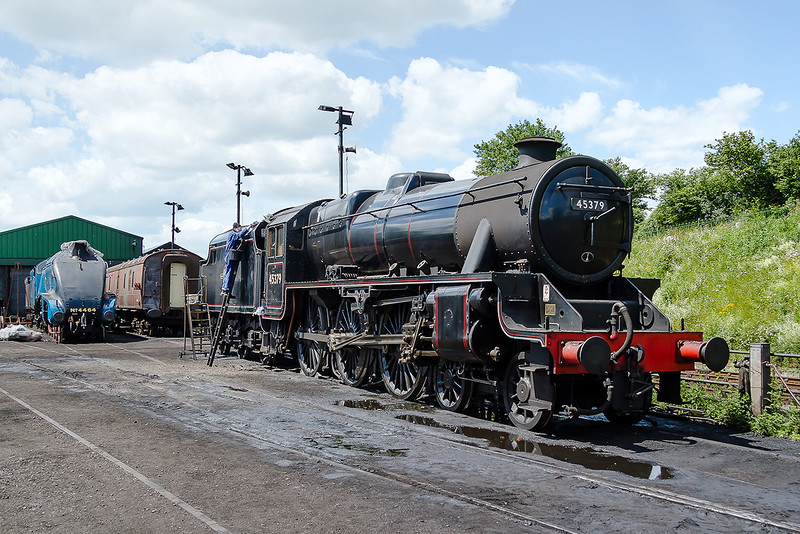 27th Jun 2015: The tender of LMS Black 5 45379 receives a little TLC while LNER A4  4464 (60019 'Bittern' with a plastic bag over the chimney rests in the background
