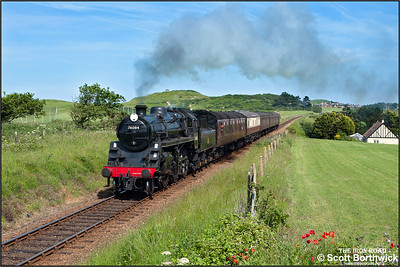 76084 runs alongside Sheringham golf course whilst working the 1500 Sheringham-Holt service on 12/06/2014.