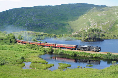 Here 62005 crosses the causeway at the western end of Loch Eilt whilst working the 1410 Mallaig-Fort William service on 02/08/2002. Proof that the sun does indeed occasionally appear in the Highlands. Both myself and my companion were being eaten alive by the midges, and it was blessed relief when the train appeared allowing us to begin the walk back to the car, and the chase to Corpach for the next shot.