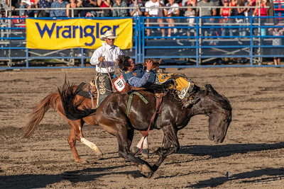 The buzzer sounds and on this occasion the cowboys bests the bucking horse!  The pickup rider comes along side and carries the cowboy to safety!