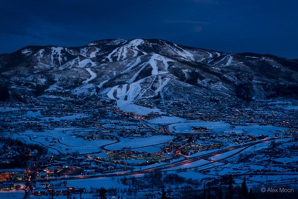 City lights glow around the base of the ski area at twilight in Steamboat Springs, Colorado.