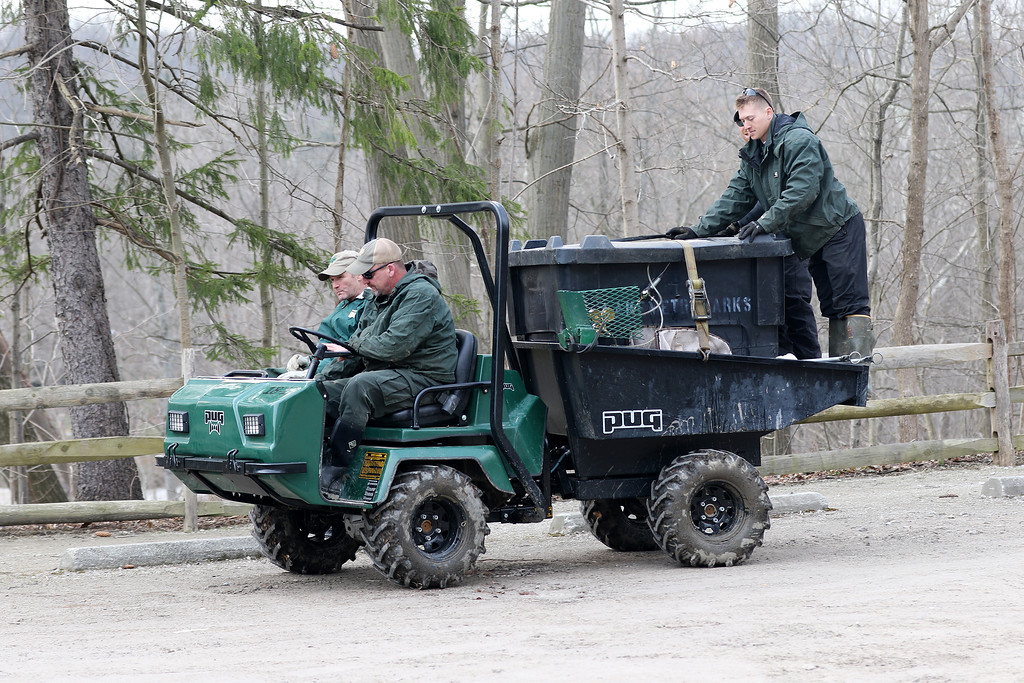 . Jonathan Tressler � The News-Herald <br> Lake Metroparks personnel leave the parking lot at Paine Falls Park in Leroy Township April 13 to access nearby Paine Creek, where they�ll stock loads of rainbow trout contained in the tank on the back of the Pug UTV on which they�re riding.