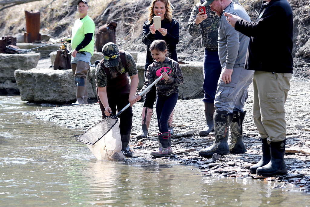 . Jonathan Tressler � The News-Herald <br> Jacob Clemens, 9, helps his 6-year-old sister, Claire, drop a few rainbow trout into Paine Creek just below Interstate 90 April 13 as Lake Metroparks performed its annual stocking of the Grand River tributary.