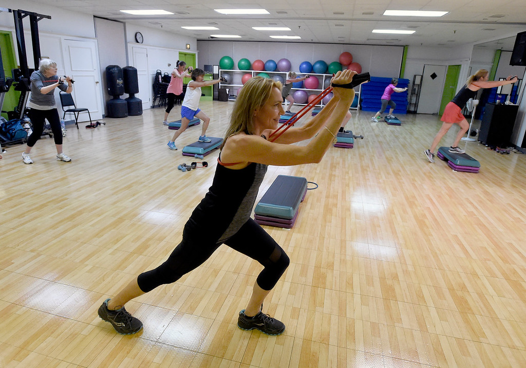 """. Dora Bannert works out during a \""""Step N\' Tone\"""" workout class on Monday at Mountains\' Edge Fitness in Boulder. For more photos of the class go to dailycamera.com Jeremy Papasso/ Staff Photographer 06/11/2018"""