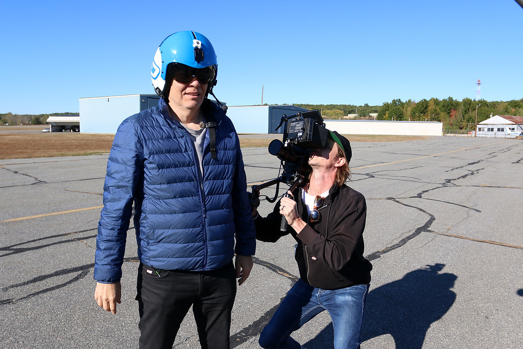 ". Stephen Baldwin was at the Fitchburg Municipal Airport on Tuesday filming his new show ""Great American Pilgrimage.\"" Max Keiser tries on the fight helmet he was going to wear in Czechoslovakian jet they had on set at the airport for the episode.  SENTINEL & ENTERPRISE / JOHN LOVE"