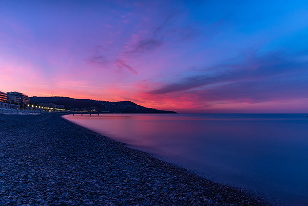 Sunrise along the pebbly shores of the Baie des Anges in Nice, France