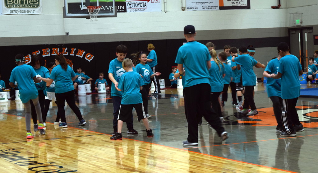 """. Coach Tyler Blood watches as Campbell Elementary fifth graders show off their secret handshakes to the song \""""Classic\"""" during the annual 5th Grade Music and P.E. Showcase Tuesday, March 12, 2019."""