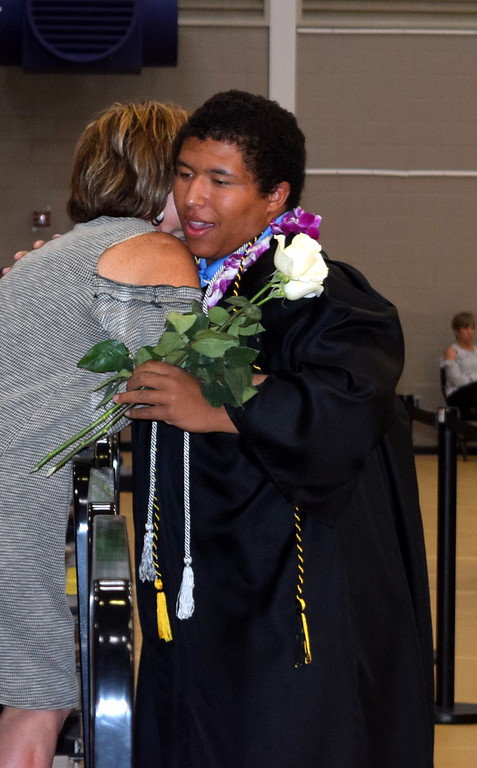. Josh Kokes gets a hug from his mother as he hands out flowers to family and friends during Caliche High School\'s Commencement Ceremony Saturday, May 25, 2019.