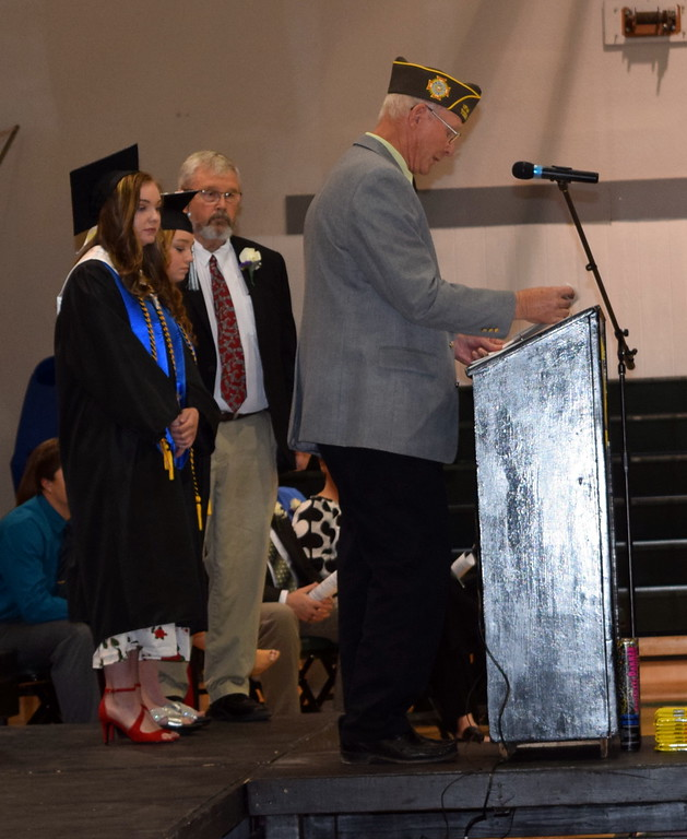 . Marvin Brekel presents the VFW scholarship to Jenna Lengfelder and Emma Seghi during Fleming High School\'s commencement ceremony Sunday, May 19, 2019. On stage with them is Fleming High School Couselor Randy Stahley.