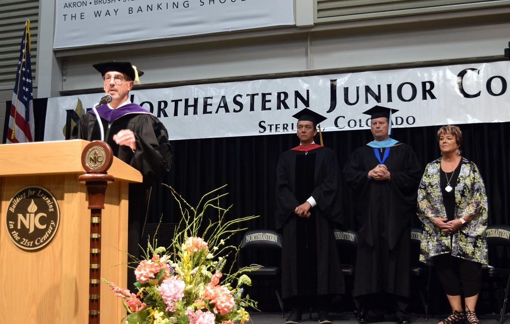 . Northeastern Junior College President Jay Lee welcomes graduates and guests to the college\'s commencement ceremony Friday, May 17, 2019. Behind him are, from left; Dr. Landon Mascareñaz, State Board for Community Colleges and Occupational Education member; John Chapdelaine, NJC Advisory Council member; and Deb Walker, NJC Alumni Association secretary.