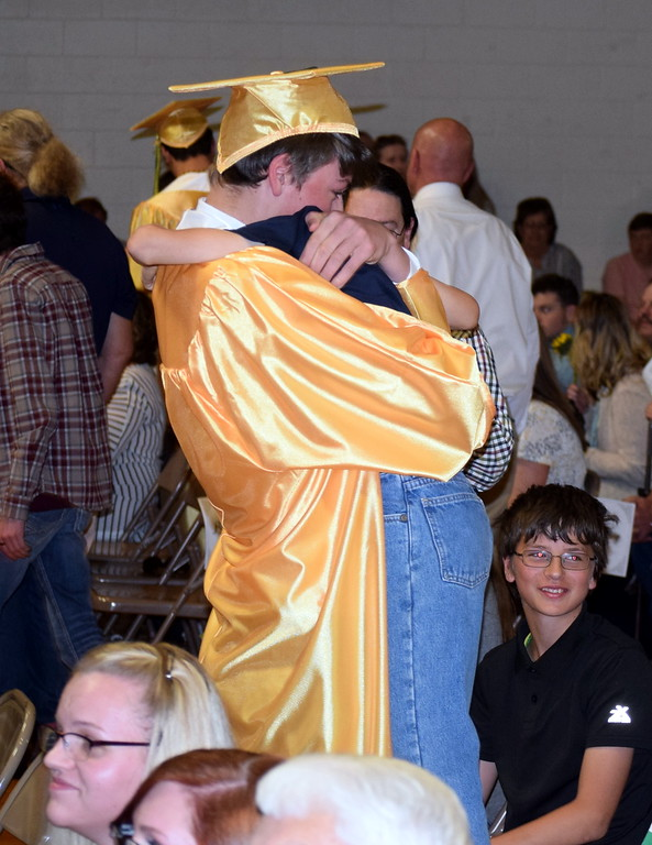 . Bryson Long gives a hug to a loved one as graduates hand out flowers to family and friends at Peetz School\'s Commencement Ceremony Sunday, May 12, 2019.