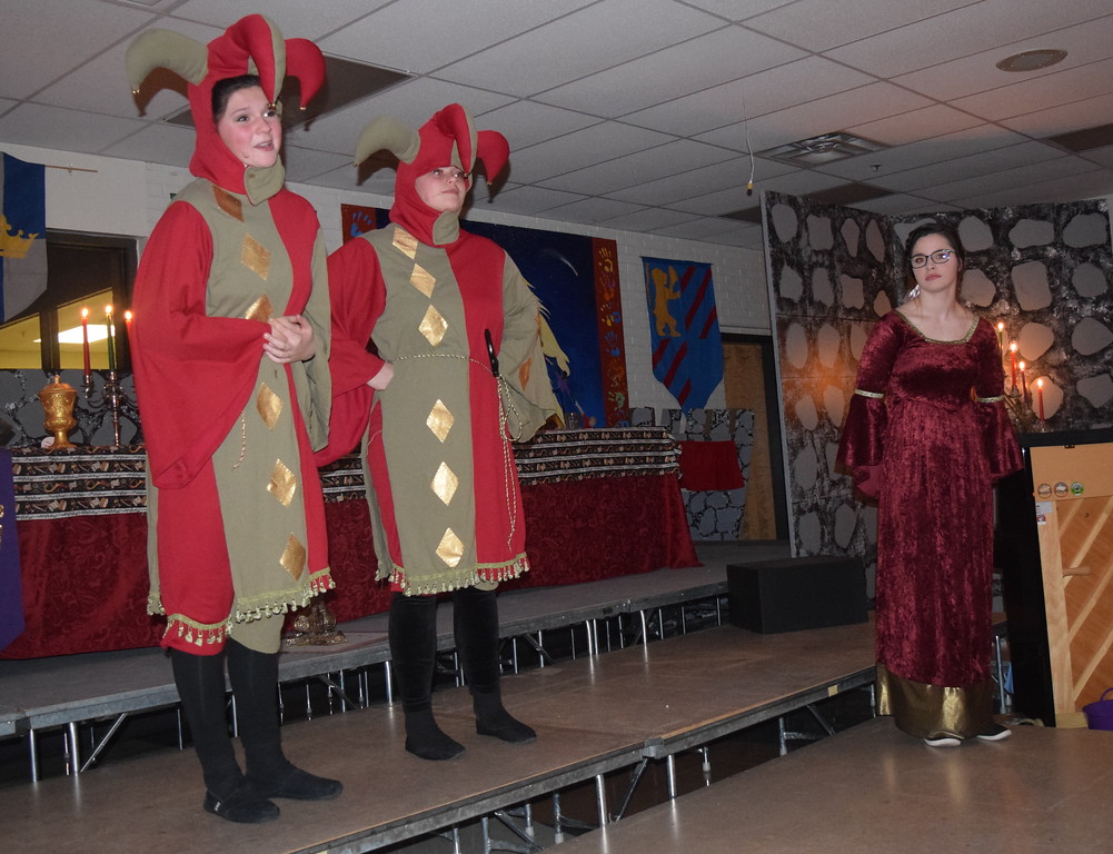. The Jesters (Katie von Steinman and Hope Jackson) welcome guests to Sterling High School\'s Madrigal Dinner Monday, Dec. 3, 2018, as the Town Crier (Colleen Wright) looks on.