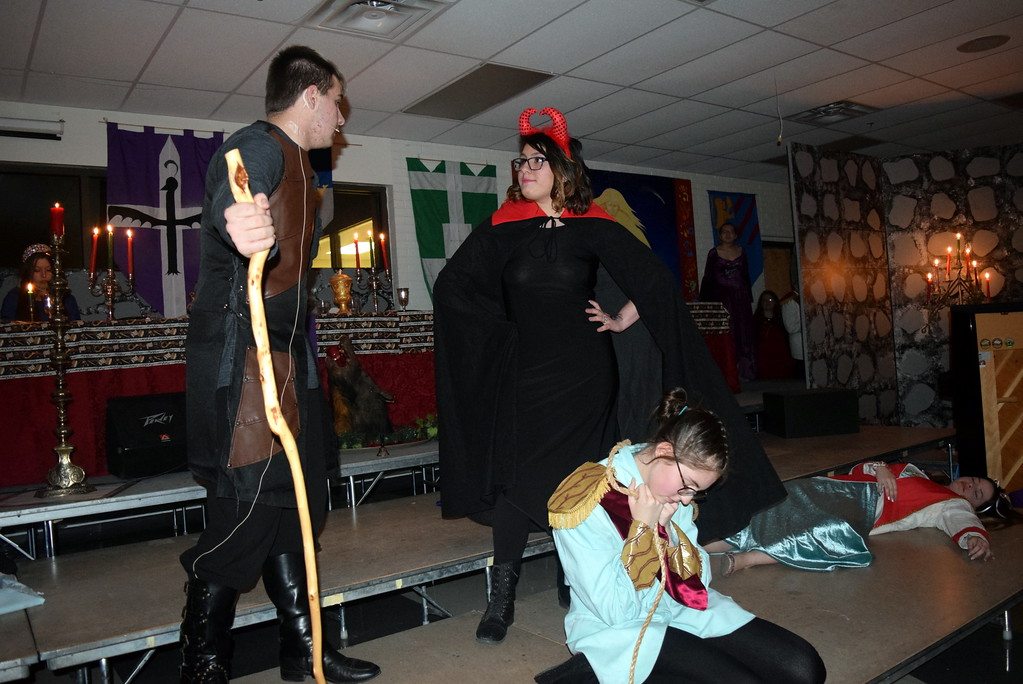 """. The Devil (Kimberly Morales) has a word with Punch #2 (Elijah Hjelm) during the theatrical production of \""""Night, Night, Knight,\"""" part of Sterling High School\'s Madrigal Dinner Monday, Dec. 3, 2018. Next to the Devil are Jack Ketch (Lindsay Butler) and Scaramouche (Cassidy Wright), who have been knocked out and put to sleep by Punch."""