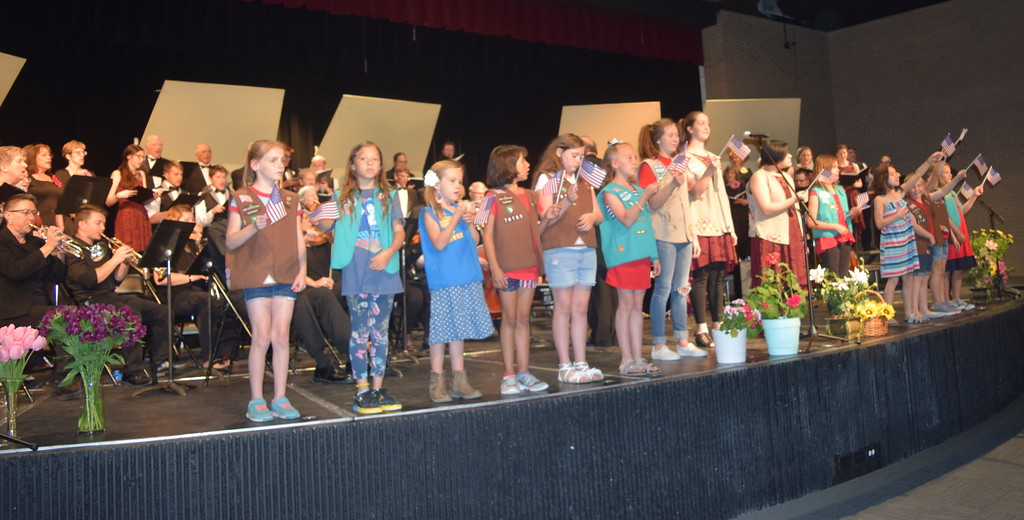 """. Girl Scout members from Troops #76180, 73910 and 82586 wave American flags as the Master Chorale and Sterling High School Jazz Choir perform \""""Battle Hymn of the Republic,\"""" under the direction of Don Johnson, at the closing of the chorale\'s 28th annual Spring Concert Sunday, May 5, 2019."""