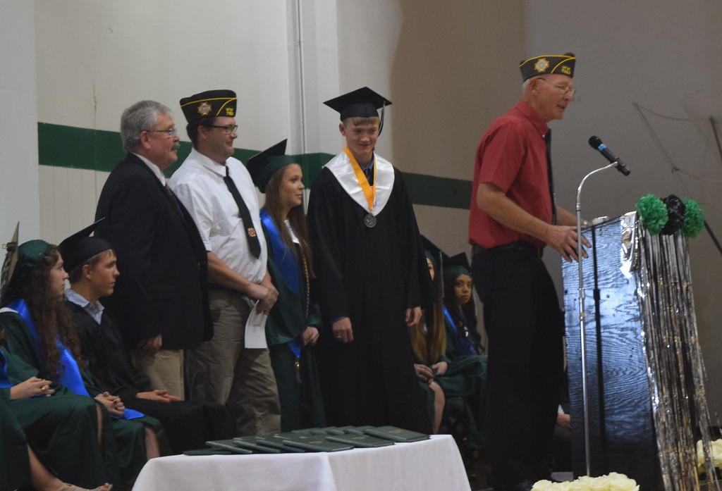 . Marvin Brekel, front and Zach Morris, back, second from left, of the Fleming VFW, present the Fleming VFW Scholarship to Alex Vandenbark and Lauryn Muller at Fleming High School\'s commencement ceremony Sunday, May 14, 2017. Joining them is Randy Stahley, FHS counselor.