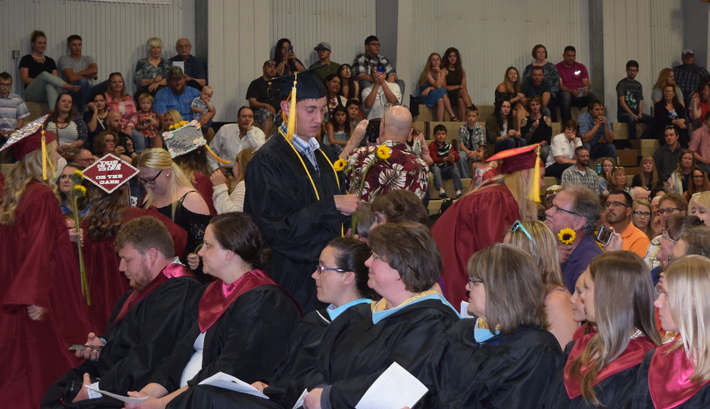 . Merino High School graduates present flowers to their family and friends during the commencement ceremony Sunday, May 20, 2018.