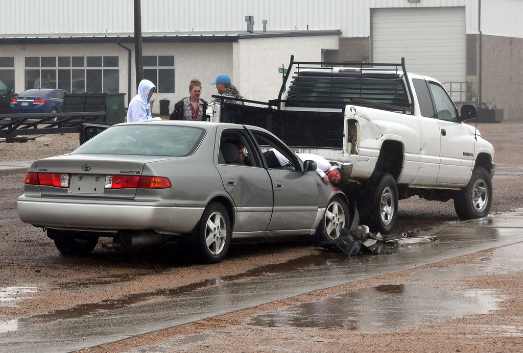 . Sedan and pickup occupants comfort while waiting for first responders, after making their way out of their vehicles, during an Every 15 Minutes program at Peetz School Tuesday, March 28, 2017.