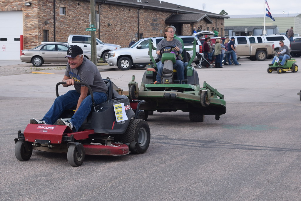". Peetz Lions Club members ride lawn mowers down the parade route during the Peetz Sake Days ""Still on the Hill\"" Centennial Parade Saturday, Sept. 30, 2017."