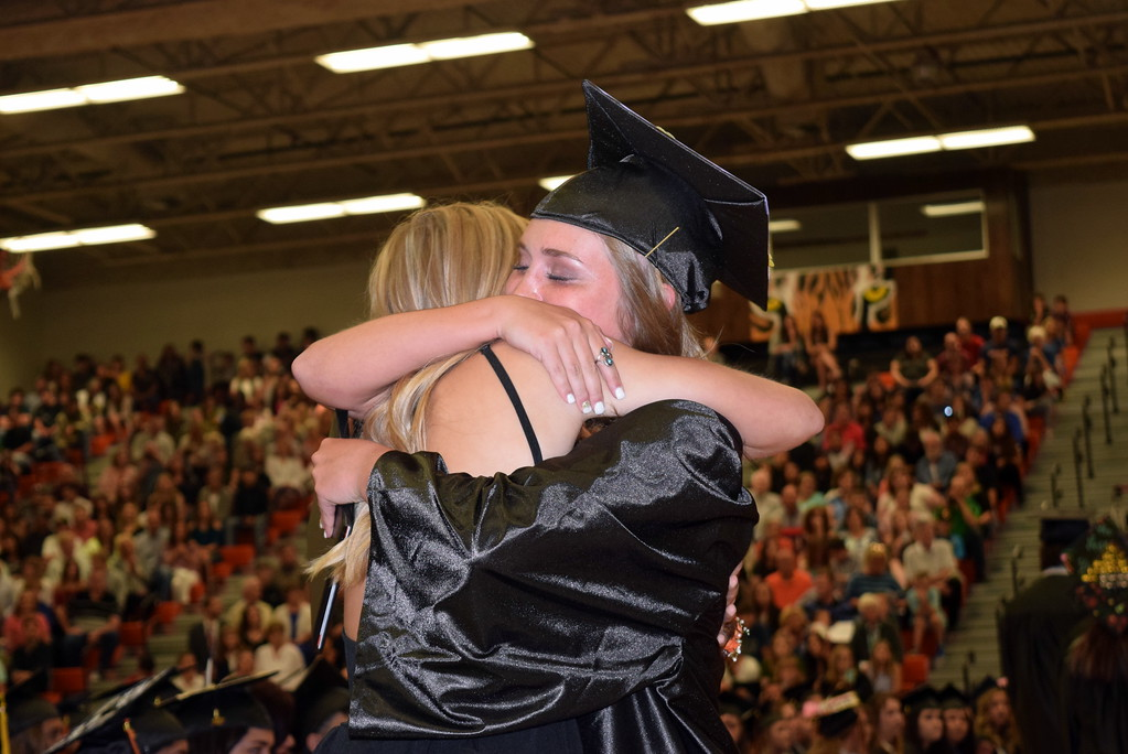 . A graduate gets a hug after receiving her diploma at Sterling High School\'s commencement exercises Saturday, May 27, 2017.