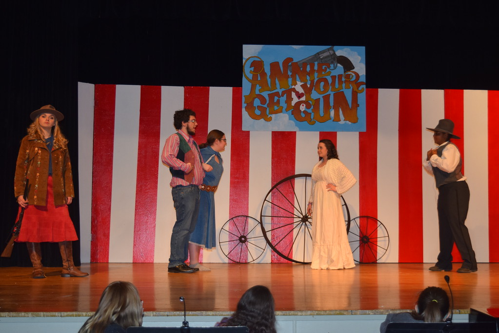 """. Winnie Tate (Camryn Trump) and her boyfriend Tommy Keeler (Christian Scott) argue with Winnie\'s sister, Dolly Tate (Grace Reeves), second from left, while Annie Oakley (Kori Penfold) and Charlie Davenport (Julia Sessanga) listen in a scene from Sterling High School\'s upcoming production of \""""Annie Get Your Gun.\"""""""