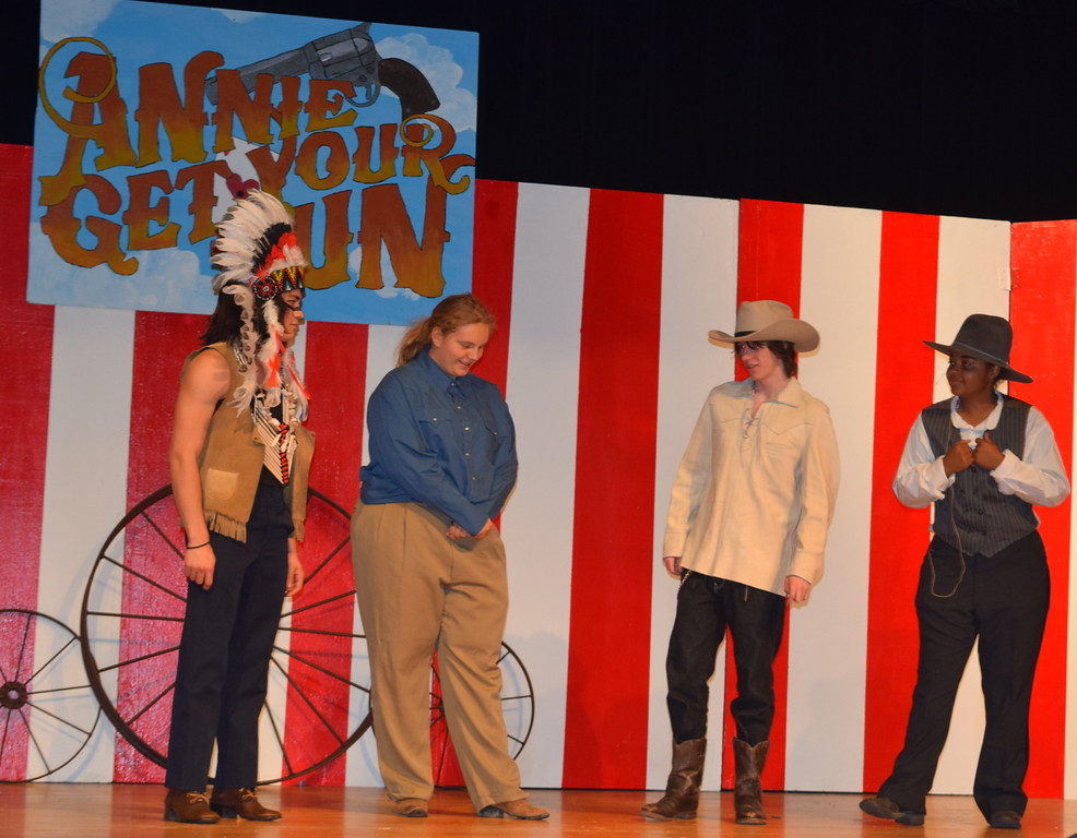 """. Buffalo Bill Cody (Clifford Farrington), second from right, has a conversation with Chief Sitting Bull (Gabriel DeLeon), left, Pawnee Bill (Mary Ritter), second from left, and Charlie Davenport (Julia Ssessanga) in a scene from Sterling High School\'s upcoming production of \""""Annie Get Your Gun.\"""""""