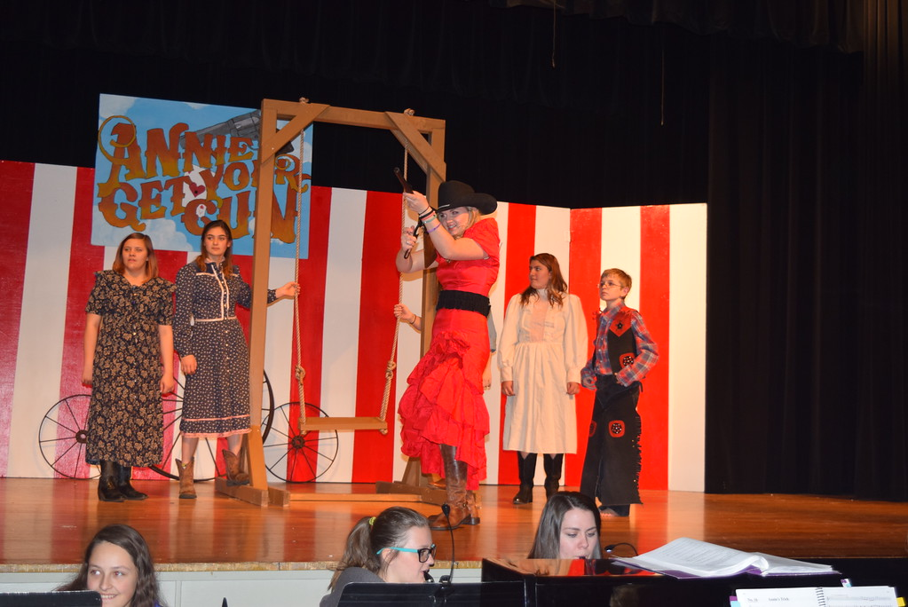 """. Sharp shooter Annie Oakley (Kori Penfold) takes a shot as her sisters and brother, Dessie (Destinly Boden), Nellie (Jaden Penfold), Jessie (Madison Trahern), Kimmie (Kimberly Morales) and Little Jake (Roland Strobel), look on, in a scene from Sterling High School\'s upcoming production of  \""""Annie Get Your Gun.\"""""""