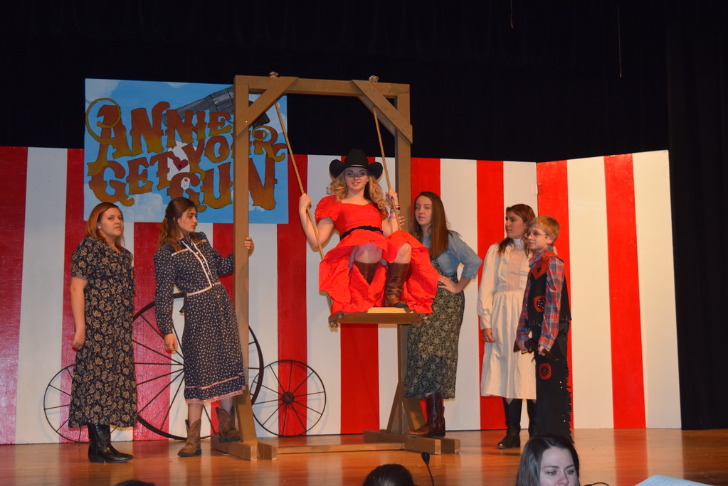 """. Annie Oakley (Kori Penfold) pulls her self up onto the seat of a swing to prepare to do a trick shot, as her sisters and brother, Dessie (Destinly Boden), Nellie (Jaden Penfold), Jessie (Madison Trahern), Kimmie (Kimberly Morales) and Little Jake (Roland Strobel), look on, in a scene from Sterling High School\'s upcoming production of \""""Annie Get Your Gun.\"""""""