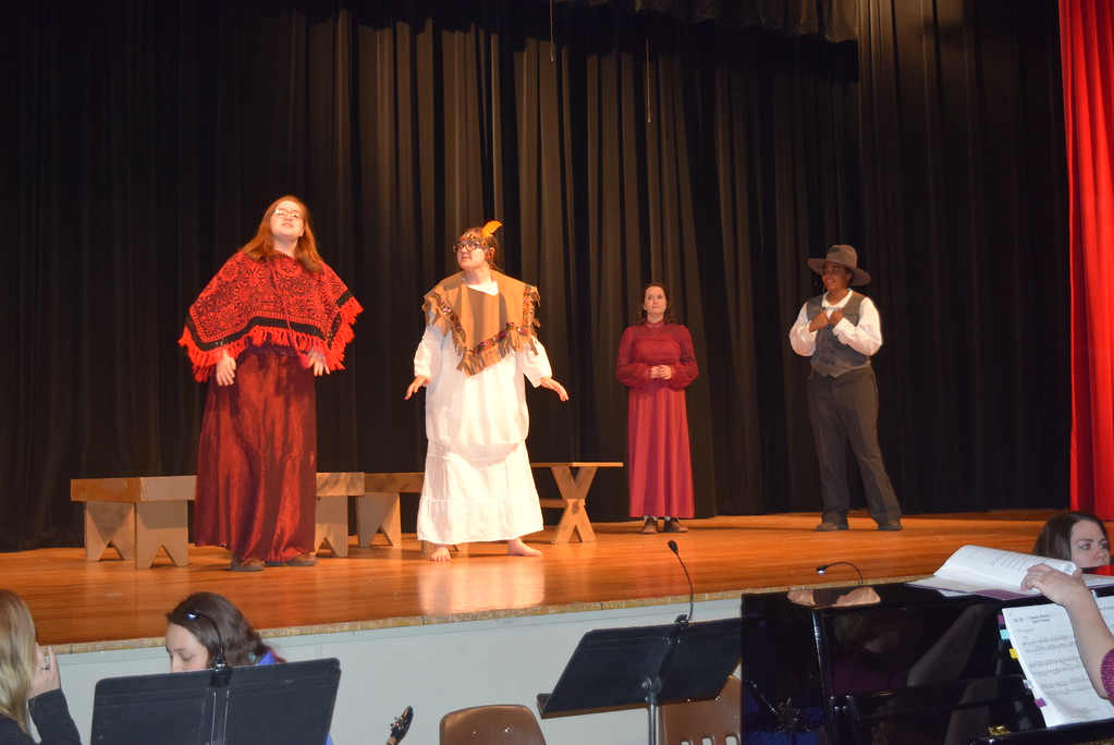 """. Running Deer (Darrian Tait), second from left, talks with Eagle Feather (Darcy Trump), as Dolly Tate (Grace Reeves) and Charlie Davenport (Julia Ssessanga) in a scene from Sterling High School\'s upcoming production of \""""Annie Get Your Gun.\"""""""