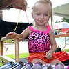2 year old Dempsey Davidson of Eastpointe, sits patiently in a chair at the Studio 9 Salon of Sterling Heights, as she has her hair wrapped at Sterlingfest '16.  Ray Skowronek--The Macomb Daily
