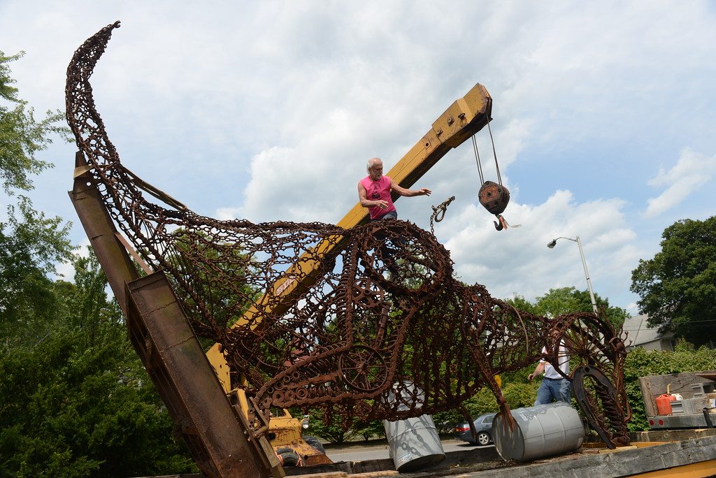 . Local artist Steve Heller of Olivebridge, N.Y., helps to load his dinosaur sculpture, �Tyrannosaurus Wrench,� onto a trailer on Aug. 7  at the intersection of Col. Chandler Drive, Albany Avenue and Broadway in Kingston, N.Y., where it has been standing since Kingston�s 2007 Sculpture Biennial.